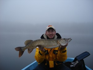 Island house guest with pike caught in lake in front of house
